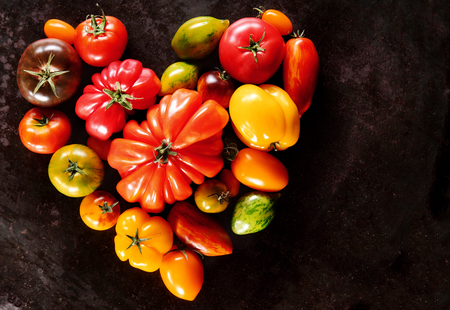 antioxidants: Assorted varieties of colorful ripe healthy tomatoes arranged in a heart shape conceptual of healthy eating and heart or a love of tomatoes as a vegetable, overhead view with copyspace