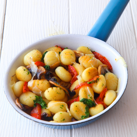 ambiente: Traditional gnocchi, or Italian semolina dumplings with tomato, mushrooms and herbs served in a blue frying pan on a white wooden table, high angle view Stock Photo