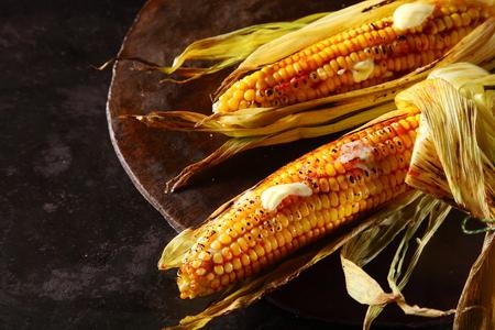 mazorca de maiz: Mazorcas de maíz asadas oa la parrilla frescas con fusión de la mantequilla a los núcleos suculentos servido sobre una placa de metal rústico, vista aérea Foto de archivo
