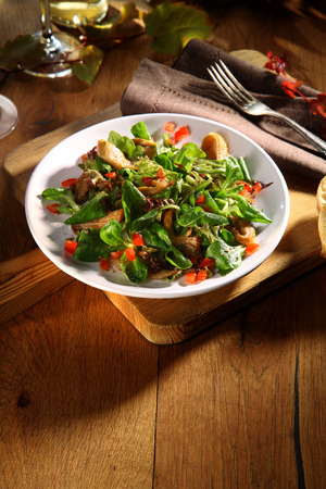 ambiente: Delicious autumn salad with fresh king oyster mushrooms and mixed leafy greens and herbs served in a bowl as a side dish or appetizer to a meal