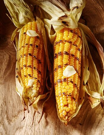 zea: Barbecued grilled fresh corn on the cob garnished with a dollop of melted butter for a healthy autumn or fall snack or appetizer, two viewed high angle