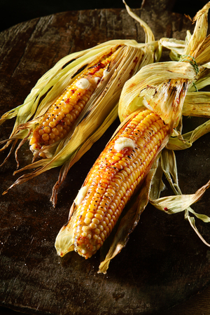 zea mays: Two healthy farm fresh grilled corncobs drizzled with melting butter on an old oven baking tray for delicious autumn or fall cuisine, high angle close up view Stock Photo