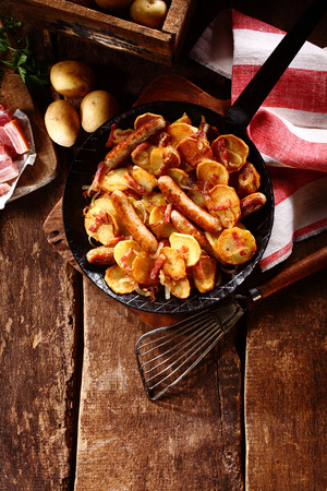 pans: Preparing tasty seasonal autumn cuisine on a rustic wooden kitchen counter with golden crispy potatoes, frankfurters and bacon in an old frying pan, overhead view