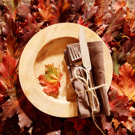 themed: Autumn themed place setting with cutlery and a brown napkin tied with string on a yellow plate over an arrangement of colorful autumn or fall leaves, square full frame overhead view Stock Photo
