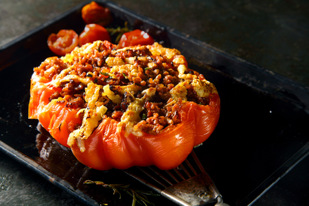 piquant: Piquant homemade stuffed roasted ripe red tomato filled with a spicy savory stuffing with cheese for a delicious starter