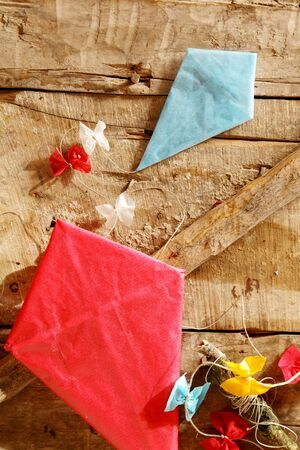paper kites: Two colorful red and blue handmade paper kites with decorative multicolored bows on the tails lying on an old wooden table with diagonal cross bar, overhead view Stock Photo