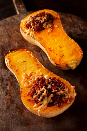 Stuffed roasted autumn butternut squash with a savory filling of beef mince, spices and cheese served halved on a wooden board in a restaurant