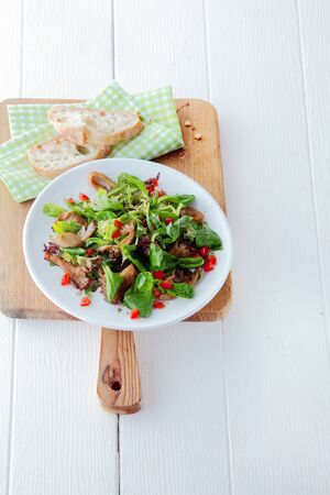 white yummy: Healthy seasonal autumn salad with king oyster mushrooms and fresh leafy greens served with bread on a wooden chopping board on a white table with copyspace Stock Photo