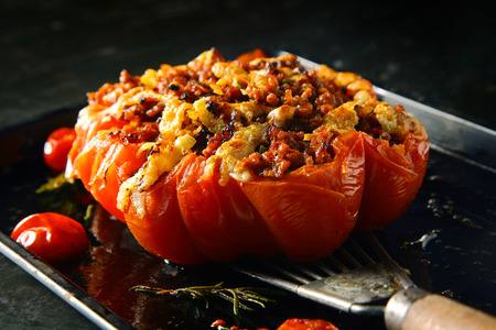 accompaniment: Appetizing stuffed oven roasted ripe tomato with a spicy savory stuffing being displayed on a spatula for healthy starters or accompaniment to dinner Stock Photo