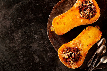 butternut: Halved roasted butternut squash with spicy filling viewed overhead on a rustic flat metal plate with spoons and copyspace for healthy seasonal autumn cuisine Stock Photo