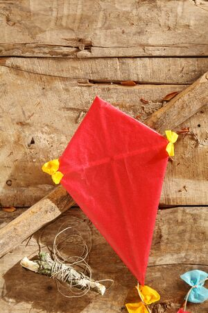 cross bar: Fun red kite for a young child with colourful yellow bows and old twine lying on a rustic wooden table with diagonal cross bar, overhead view with copyspace