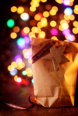 christmasy: Simple Christmas gift in a brown paper bag tied with a Merry Christmas ribbon and star on a wooden table with a colorful party bokeh of sparkling lights in the background