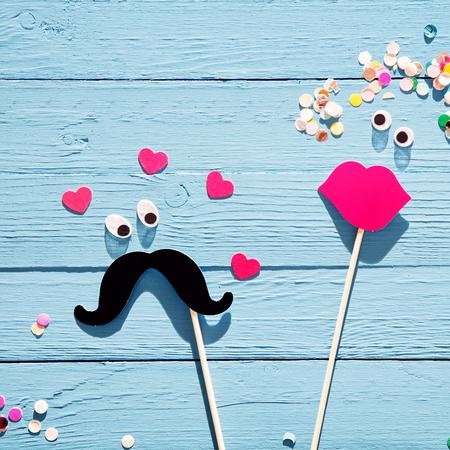 carnaval: Diversi�n pareja rom�ntica de los accesorios de la cabina de fotos con un bigote con los ojos rodeados de corazones mirando a una mujer con los labios rojos deliciosos y flores confeti en el pelo, en un fondo de madera azul r�stico