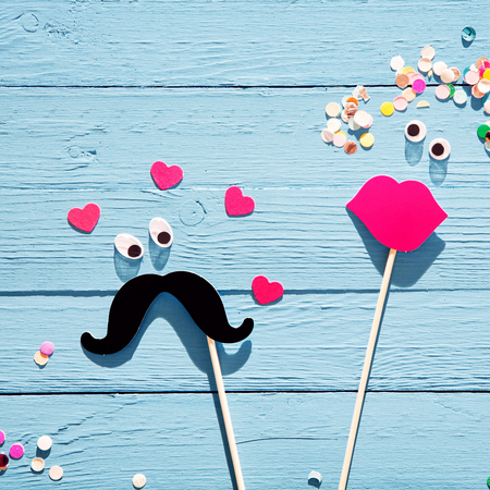 photo of accessories: Fun romantic couple from photo booth accessories with a mustache with eyes surrounded by hearts eyeing a lady with luscious red lips and confetti flowers in her hair, on a rustic blue wood background Stock Photo