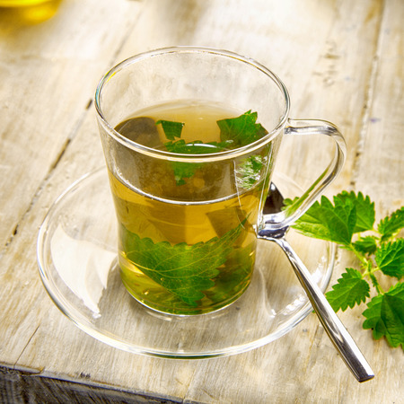 stinging nettle: Cup of healthy stinging nettle tea with fresh nettle leaves steeping in boiling water in a clear glass mug on an old wooden table Stock Photo