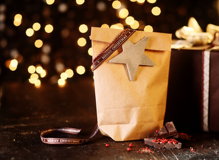 ambiente: Decorative simple country Christmas gift in a brown paper package sealed with ribbon and a star on a wooden counter against a backdrop of sparkling golden Xmas lights in a soft bokeh