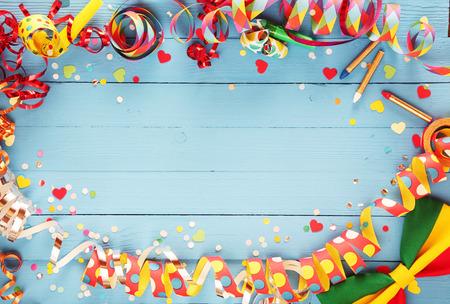 お祝いパーティの罫線またはカラフルなスパイラル吹流しと紙吹雪のコーナー、copyspace で蝶ネクタイをした素朴な古い青い木製の背景上に配置のフ 写真素材