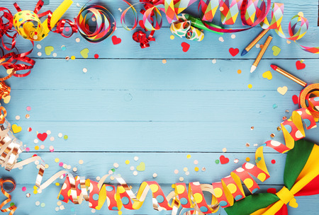 carnival party: Festive party border or frame of colorful spiral streamers and confetti arranged on a rustic old blue wooden background with a bow tie in the corner and copyspace