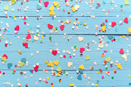 Blue wood background with scattered colorful party confetti with heart shapes in a closeup full frame overhead view for festive or celebration themed concepts Stockfoto