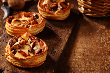 cooked: Three delicious fresh mushroom tarts in puff pastry bases prepared from assorted healthy seasonal autumn fungi, high angle view