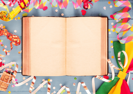 spread around: Artistic party card or invitation background with a colorful frame of spiral streamers, confetti, a champagne cork and bow tie around an open book with double spread blank pages for your text