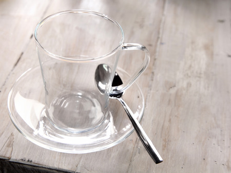 glass cup: Empty clear glass mug or cup and saucer standing ready with a teaspoon on an old weathered wood table for making a cup of hot refreshing tea Stock Photo
