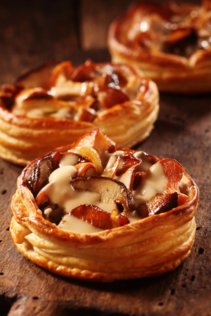 Gourmet mushroom tart in a crisp golden puff pastry base prepared with assorted edible fall or autumn fungi