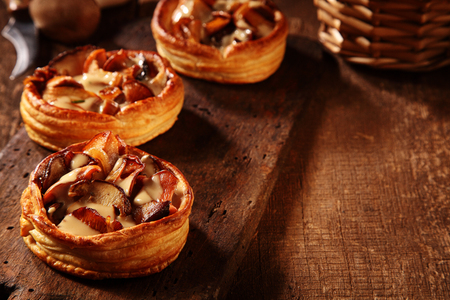 bases: Gourmet fresh mushroom tarts prepared with assorted seasonal autumn or fall fungi in a creamy sauce in crispy puff pastry bases Stock Photo