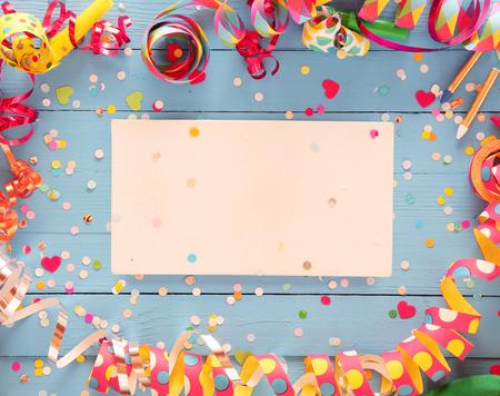 Decoratief partij frame van kleurrijke spiraal slingers en confetti over een rustieke houten blauwe achtergrond met centrale blanco kaart met copyspace voor uw begroeting of uitnodiging