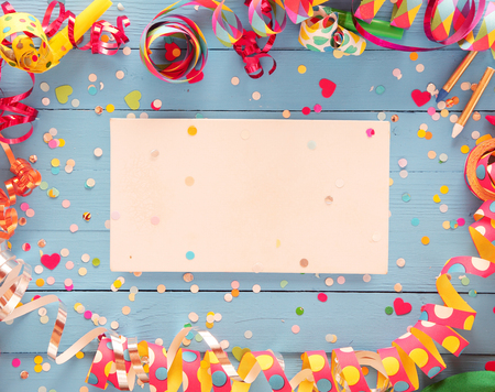 Decorative party frame of colorful spiral streamers and confetti over a rustic blue wood background with central blank card with copyspace for your greeting or invitation