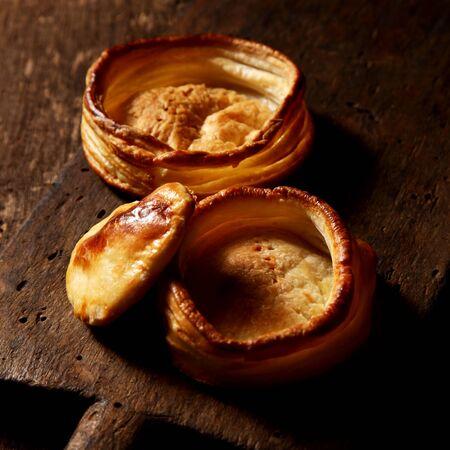 pasteles: Casos de hojaldre dorado pastelería tarta crujiente recién horneados a la espera de ser llenado con un relleno salado en una vieja mesa de madera rústica, uno con una tapa entornada junto