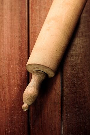 cooking implement: Overhead view of an old wooden rolling pin on a kitchen table in a concept of baking and cooking food Stock Photo