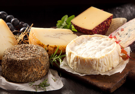 speciality: Delicious array of gourmet cheese on a platter with an assortment of uncut speciality regional cheese, soft and semi-hard wedges Stock Photo