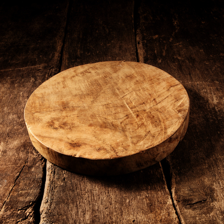 Old empty round rustic wooden cheese board with deeply scored cuts and stains on a rustic wooden table with copyspace for your placement of products or advertising Banque d'images