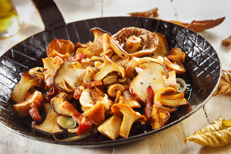 accompaniment: Seasonal autumn cooking with a frying pan full of sliced assorted freshly harvested mushrooms for a gourmet accompaniment to a meal or appetizer Stock Photo