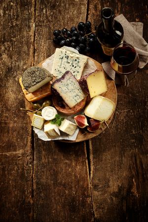 queso: Gourmet plato de queso con una amplia variedad de crema suave y semi-duras quesos, así como variedades de especialidades gourmet, vista de ángulo alto sobre una mesa de madera rústica con copyspace