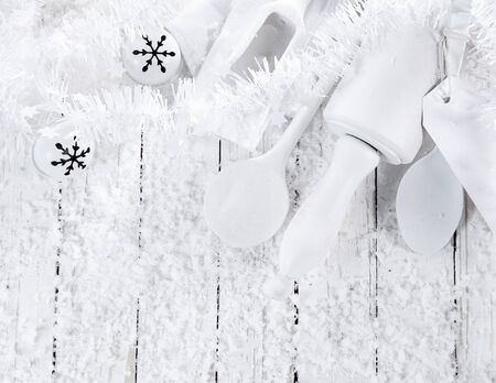 seasonal greeting: Monochrome seasonal Christmas all white winter baking concept with pure white wooden baking utensils with Xmas baubles and scattered winter snow on a white table with copyspace for a seasonal greeting