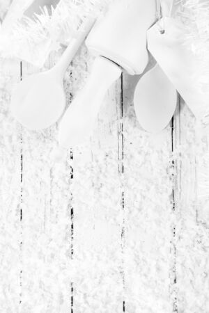 top angle: Monochromatic seasonal Christmas white cooking or baking concept with pure white wooden utensils decorated with white tinsel on a white wooden table with winter snow and copyspace, overhead view