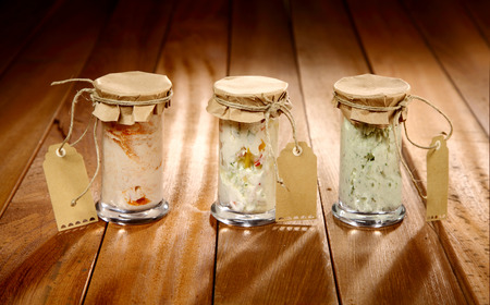 dips: Three rustic glass jars of three homemade creamy savory dips as gifts with a brown paper seal and blank gift tags tied with string in a line on a wooden table Stock Photo