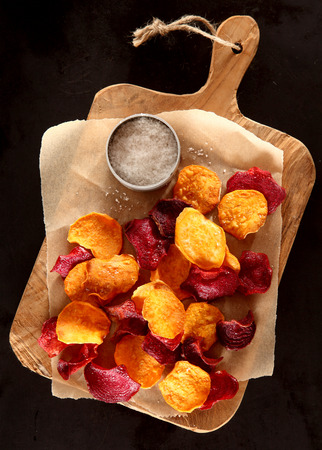 appetiser: Tasty healthy crisp crunchy beetroot and potato chips served on a rustic wooden board with coarse rock salt for a vegetarian snack, or appetiser, overhead view on black Stock Photo
