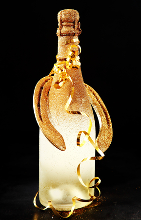 unlabelled: New Year or Wedding Good Luck greeting card design with a frosted golden bottle of champagne and lucky horseshoe on a black background decorated with a spiral gold party streamer