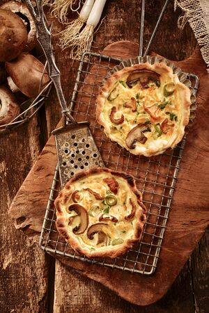 country kitchen: Speciality autumn cuisine with fresh fungi or forest mushrooms prepared in savory tarts with puff pastry bases, overhead view in a rustic country kitchen Stock Photo