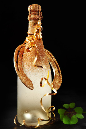 unlabelled: Golden bottle of chilled frosted festive champagne and horseshoe for Good Luck tied with spiral gold party streamers over a black background with a green Irish shamrock