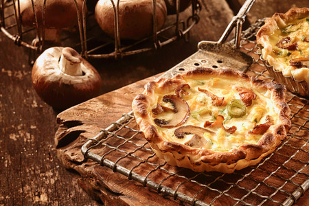 gourmet kitchen: Gourmet mushroom tart with autumn fungi fresh from the forest in a crispy pastry crust cooling on a metal tray in the kitchen Stock Photo