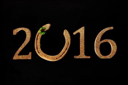 herradura: 2016 Año Nuevo fondo deseándole buena suerte con una herradura de oro incorporado a la fecha con un trébol de cuatro hojas verde o trébol en un fondo negro Foto de archivo