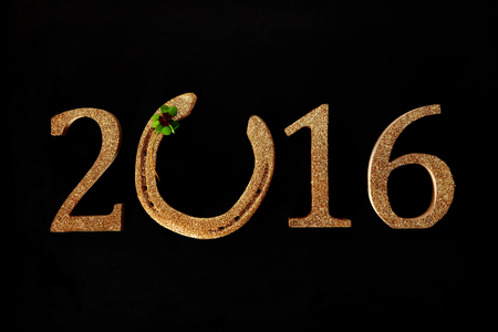 shamrock: 2016 New Year background wishing you Good Luck with a golden horseshoe incorporated into the date with a green four-leaf clover or shamrock on a black background Stock Photo