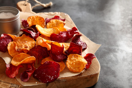 Crisp crunchy organic vegetable chips with fried or oven-baked potato and beetroot chips served as a finger food snack on a wooden chopping board with sea salt and copyspace