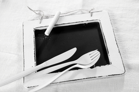 the recipe to write down: All white place setting concept with white utensils lying on a vintage school slate with white border over textured white textile, high angle view with copyspace on the slate Stock Photo