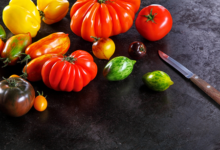knife tomato: Assorted varieties of ripe fresh tomato in different shapes and bright colors arranged in the corner of the frame on an old textured dark surface with a kitchen knife and copyspace