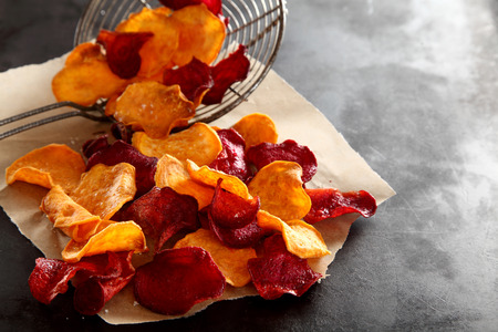 ovenbaked: Crisp crunchy fresh fried beetroot chips in a vintage wire strainer placed on paper to cool on a dark textured kitchen counter, high angle with copyspace